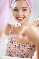 schöne junge Frau, die ihre Zähne putzt foto