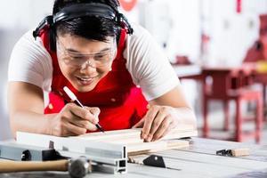asiatischer chinesischer Zimmermann, der Holz mit Säge schneidet foto
