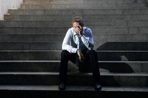 Geschäftsmann weint verloren in der Depression, die auf Straßenbetontreppen sitzt