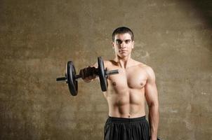 junger Mann, der Gewichte in der Turnhalle trainiert foto