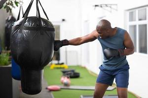 afrikanischer Mann, der mit Boxsack trainiert foto