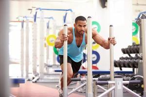 muskulöser Mann, der mit Geräten in einem Fitnessstudio trainiert foto
