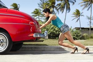 Frau drückt kaputtes altes Auto foto