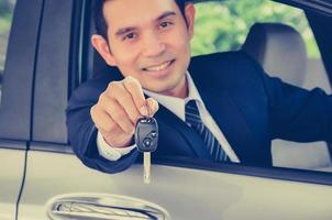 asiatischer Geschäftsmann, der einen Autoschlüssel gibt - Weinlese-Ton foto