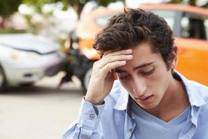 besorgter jugendlicher Fahrer, der nach Verkehrsunfall mit dem Auto sitzt foto