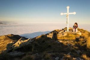 Frau, die auf dem Berggipfel ruht foto