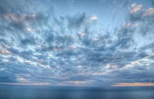 expansive Wolken über einem ruhigen Ozean bei Sonnenuntergang foto