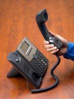 Person, die den Telefonhörer in der Hand hält foto
