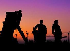 Die Gruppe der Arbeiter, die auf einer verschwommenen Baustelle arbeiten. foto