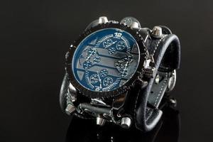Nahaufnahme der Armbanduhr auf einem schwarzen Hintergrund foto