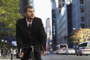 Geschäftsmann, der Fahrrad fährt, während wegschaut foto