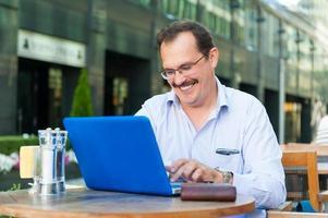 Geschäftsmann mittleren Alters arbeitet am Laptop foto