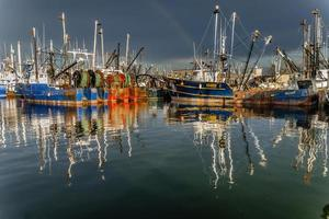 Fischereifahrzeuge nach Sturm mit Regenbogen