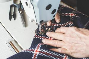 Frau näht auf einer Nähmaschine. foto