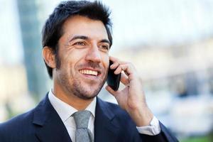 schöner Geschäftsmann, der auf dem Handy spricht foto