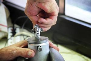 Juwelier prägt Silberdekoration in der Werkstatt foto