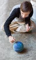 attraktiver Junge mit Autismus dreht einen Ball foto