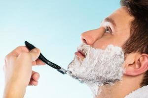 Mann, der sich mit Rasiermessergesichtsprofil rasiert foto