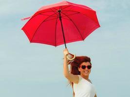 rothaariges Mädchen, das mit Regenschirm am Strand springt foto