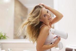 natürliche blonde Frau, die Haare im Badezimmer trocknet foto