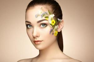 Gesicht der schönen Frau mit Blumen geschmückt foto