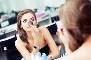 Frau scherzt vor einem Spiegel
