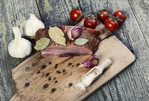 geräuchertes Schweinefleisch mit Kräutern und Gewürzen auf Holzbrett foto