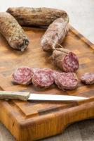 italienische Salami-Scheiben auf Schneidebrett mit Küchenmesser foto