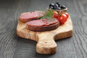 Roggenbrot mit Salami auf Olivenbrett foto