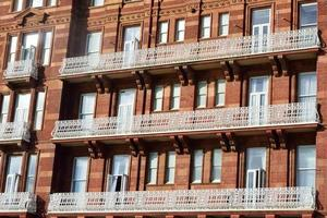 Hotel aus rotem Backstein mit weißem Balkon foto