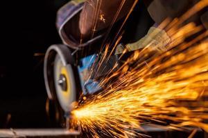 Nahaufnahme des Arbeiters, der Metall mit Schleifmaschine schneidet foto