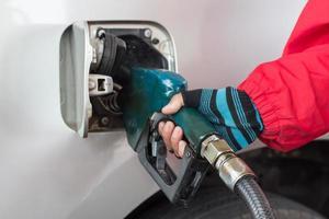 Hand das Auto an einer Tankstelle mit Kraftstoff auffüllen