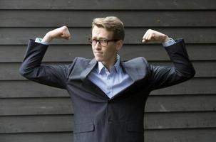 junger Geschäftsmann, der seine Muskeln spannt foto