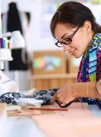 Modedesigner, der Textilien neben einer Nähmaschine schneidet foto