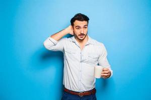 schöner erwachsener Mann, der Freizeitkleidung auf blauem Hintergrund trägt foto