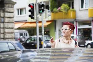 Porträt der rothaarigen Frau auf der Straße, die Zigarette raucht