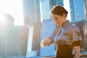 Geschäftsfrau, die die Zeit überprüft foto
