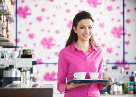 junge lächelnde Kellnerin, die Kaffee an der Bar serviert