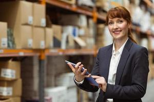 lächelnde Geschäftsfrau, die auf digitalem Tablett rollt foto