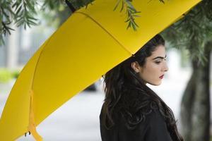 Frau, die beiseite steht und gelben Unbrella hält foto
