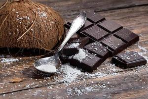 Schokolade und Kokosnuss auf altem Tisch foto