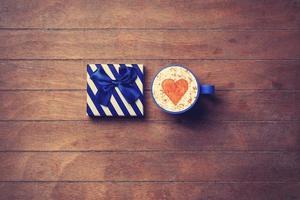 Tasse und Geschenkbox auf hölzernem Hintergrund