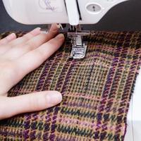 Hand und Fuß der Nähmaschine auf Wolltuch foto
