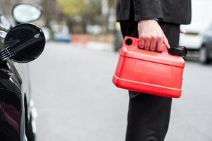 Mann, der Kraftstoffdose hält, beschnittenes Bild foto