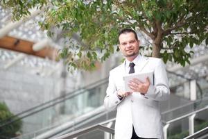 schöner Geschäftsmann mit digitalem Tablet foto