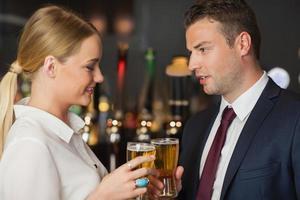 Kollegen stoßen ihre Gläser Bier an foto