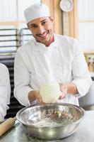 Bäcker, der Teig in Rührschüssel bildet foto