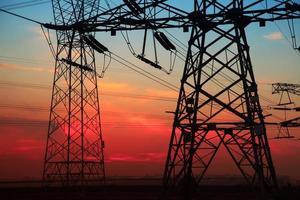 die Silhouette des abendlichen Stromübertragungspylons foto