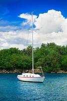 Segelfischyacht in der Nähe der malerischen grünen Insel foto