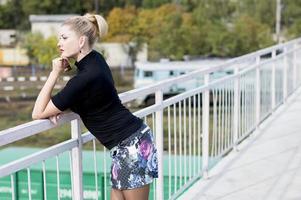 Frau in einem Minirock auf der Brücke, die fern schaut